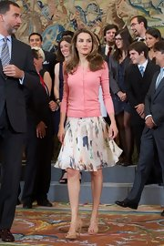 Princess Letizia attended an audience at Zarzuela Palace looking casual yet sweet in nude strappy sandals, a flared skirt, and a pink cardigan.