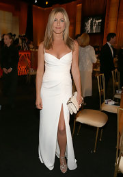 Jennifer Aniston styled her dress with strappy snakeskin heels by Tabitha Simmons.