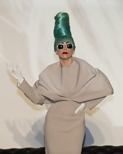 Lady Gaga teamed white leather gloves with a beige dress and a sky-high green 'do for a press conference in Singapore.