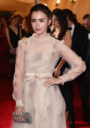 Lily Collins looked dreamy at the Met Gala sporting this Valentino snakeskin clutch and gown combo.