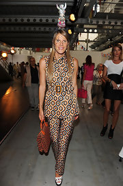 Anna dello Russo wasn't afraid of clashing prints, pairing her pantsuit with a two-tone patterned fabric briefcase.