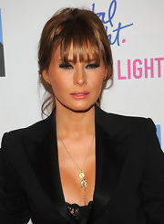 Melania Trump adorned her decolletage with a pair of gold pendants.
