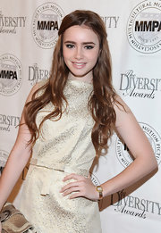 Lily Collins attended an Oscar luncheon wearing a gold quartz watch to complement her jacquard dress.