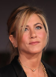 Jennifer Aniston accessorized with layers of necklaces, including a delicate pearl pendant.