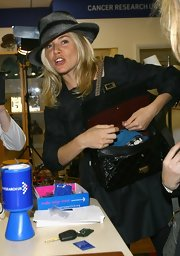 Sienna Miller looked a little mysterious in her striped fedora while attending the Make Today Count auction.