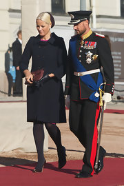 Princess Mette-Marit opted for a double-breasted black coat when she attended the official welcome ceremony at the Royal Palace during Finnish state visit.