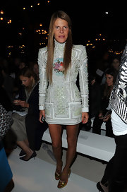 Anna dello Russo attended the Balmain fashion show looking bold in a high-neck, pearl-studded white mini from the label.