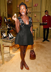 Shala Monroque complemented her dress with a brown crocodile bucket purse.