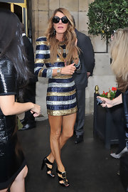 Anna dello Russo sported a striking silhouette in a sequined Balmain mini in gold, silver, and blue stripes during the Balenciaga show.