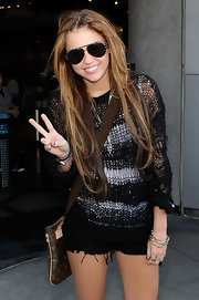 Miley Cyrus enjoyed a day out at Universal Studios carrying a Louis Vuitton monogram cross-body bag.
