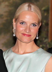 Princess Mette-Marit styled her hair into a center-parted chignon for an official dinner at the Norwegian Royal Palace.