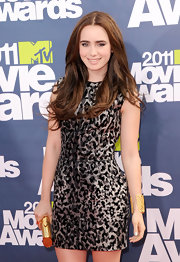 Lily Collins went for gold accessories, including a meshwork bracelet and a hard-case clutch, when she attended the MTV Movie Awards.