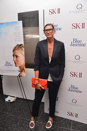 Jenna Lyons avoided a monotonous look by accessorizing with a bright orange leather clutch.