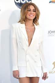Miley Cyrus teamed some statement rings with a plunging white blazer for her 2012 Billboard Music Awards look.