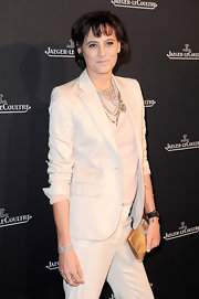 Ines de la Fressange appeared at the opening of Jaeger-LeCoultre's boutique wearing a pantsuit styled with a gold Roger Vivier clutch.