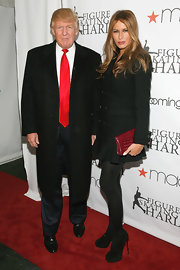 Melania Trump punctuated her black look with a red croc-embossed clutch.