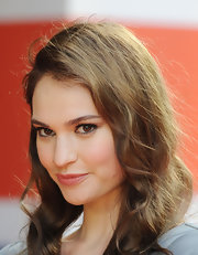 Lily James enhanced her amber eyes with natural looking lashes and dark liner.
