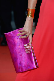 Ines de la Fressange complemented her flowy maxi dress with a glam purse and a gold cuff at Cannes.
