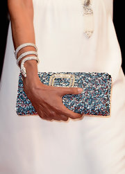 Ines de la Fressange wrapped her wrists with a diamond-studded snake bangle.