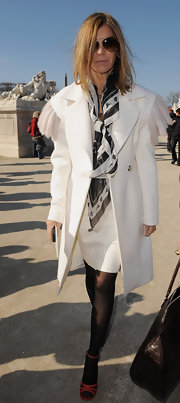 Carine Roitfeld styled her all-white outfit with a patterned scarf for a chicer finish.