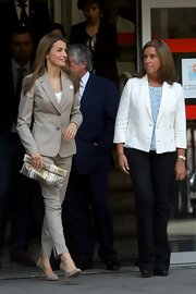 Princess Letizia added a touch of glamour to her look with a gold and silver clutch.