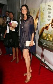 Famke Janssen matched her baby doll dress with a pair of brown slip-on sandals.