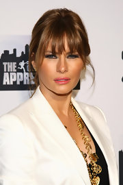 Melania Trump lit up her beautiful face with a swipe of bright pink lipstick.