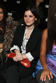 Rachel Bilson teamed a crescent-shaped red clutch with a black pantsuit for the Zac Posen fashion show.