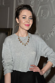 Ulyana Sergeenko styled her casual top with a gold charm necklace for the Jean Paul Gaultier fashion show.