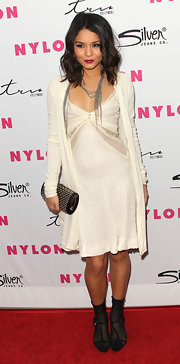 Vanessa Hudgens toughened her sweet sip dress with a black studded roll clutch.