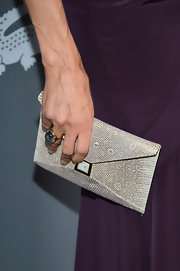 Famke Janssen attended the 15th Costume Designers Guild Awards in a purple gown styled with a sleek python skin purse.
