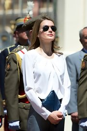 Princess Letizia attended a military event carrying a blue crocodile envelope clutch.