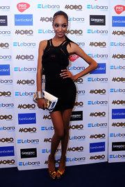 A silver metal-embellished clutch added a futuristic feel to Jourdan Dunn's look.