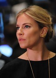 Sienna Miller visited the New York Stock Exchange wearing a classic loose bun.