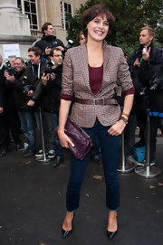 Ines de la Fressange carried a purple leather clutch at Paris Fashion Week.