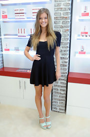 Nina Agdal cut a youthful figure in a black skater dress while promoting the European Wax Center.