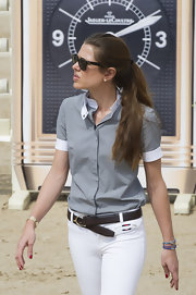 Charlotte Casiraghi teamed a brown leather belt with white pants and a gray shirt for the Global Champions Tour 2012.