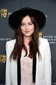 Dakota Johnson spiced up her look with a wide-brimmed black hat when she attended the BAFTA LA garden party.