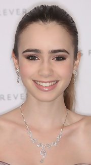 Lily Collins accessorized with a beautiful diamond necklace and matching earrings for a more glamorous finish.