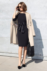 Kasia Smutniak arrived for the Giorgio Armani fashion show wearing a classic nude coat over a bow-embellished LBD.