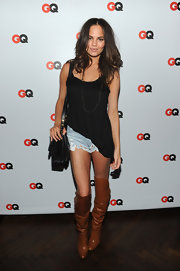 Chrissy Teigen was dressed down in an asymmetrical black tank top and ripped jean shorts during the GQ special issue party.