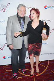 Cyndi Lauper posed at the arrivals of the Drama League Awards wearing a black top, a print skirt, and bright red slingbacks with heart embellishment.