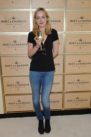 Dakota Johnson visited the Moet & Chandon suite dressed down in a plain black tee.