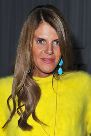 Anna dello Russo wore dangling turquoise earrings with a bright yellow outfit for some beautiful color blocking.