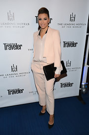Eva Longoria styled her suit with a large black envelope clutch.