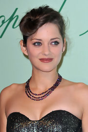 Marion Cotillard paired a layered gemstone necklace with a strapless outfit for the Chopard 150th anniversary party.