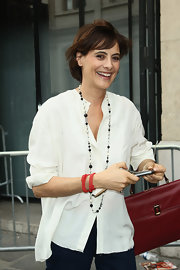 Ines de la Fressange attended Jean-Paul Gaultier's Haute Couture presentation wearing a sheer button down shirt and a pair of denim pants.
