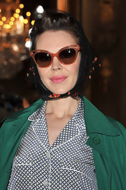 Ulyana Sergeenko attended the Stella McCartney fashion show wearing a floral-embroidered head scarf.