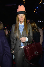 Anna dello Russo accessorized with a super-sophisticated burgundy crocodile tote by Paula Cademartori during the Dsquared2 fashion show.
