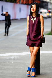 Nicole Warne jumped in on the color-block trend, teaming cobalt ankle-cuff sandals with her purple shorts/blouse combo.